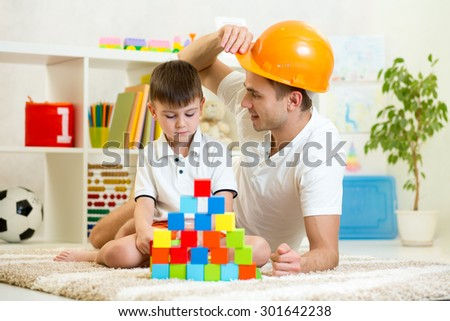 Father and child playing construction game together at home. - stock photo