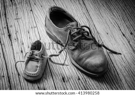 father and child shoes tie the shoestring together in heart shape, love and bound concept ( black and white tone )