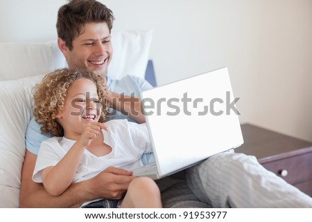 Father and child using laptop together in bed - stock photo