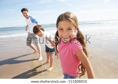 Father And Children Having Fun On Beach Holiday - stock photo
