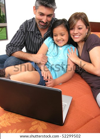 Father and children lying on the bed at home and looking into a portable computer