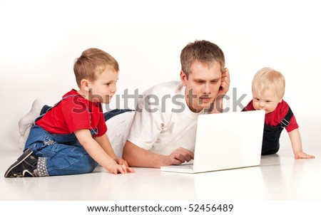 Father and children lying on the floor with laptop on white background