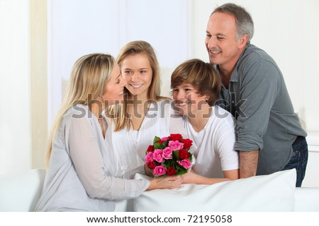 Father and children offering bunch of flowers on mother's day - stock photo