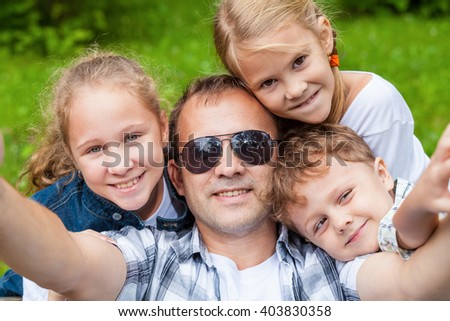 Father and children  playing at the park at the day time. Concept of friendly family. - stock photo