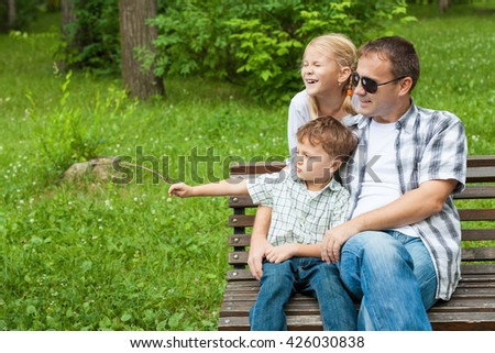 Father and children  playing at the park at the day time. Concept of friendly family.