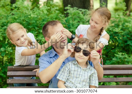 Father and children  playing at the park on bench at the day time. Concept of friendly family. - stock photo