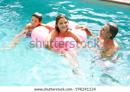 Father and children playing games and having fun in a holiday swimming pool, swimming and sharing an inflatable pink ring during a sunny summer day. Family activities and fun outdoors, lifestyle.