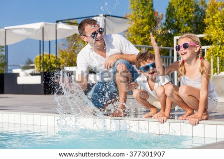 Father and children playing near a swimming pool  at the day time. Concept of friendly family.