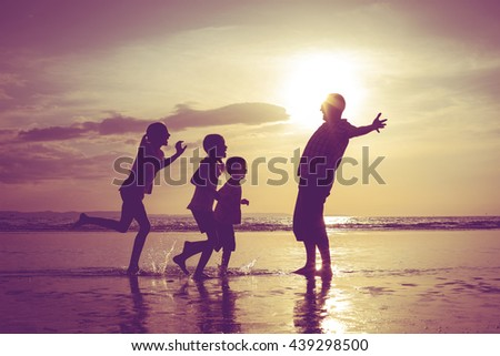 Father and children playing on the beach at the sunset time. People having fun on the sea. Concept of friendly family and of summer vacation.