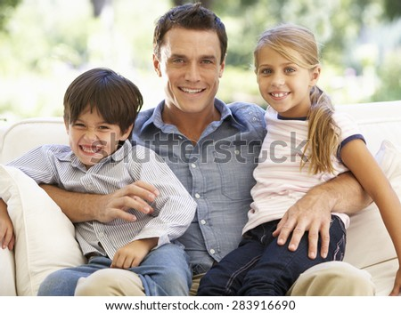 Father And Children Sitting On Sofa At Home - stock photo