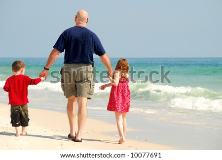 Father and Children strolling on beach - stock photo