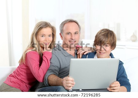 Father and children using laptop computer at home