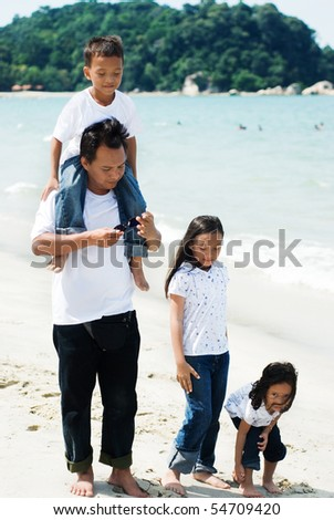 father and children walking on the beach - stock photo