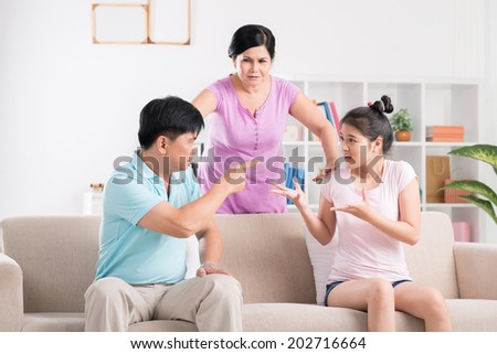 Father and daughter are fighting while mother is trying to calm them - stock photo