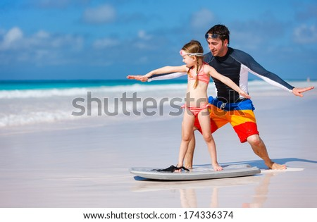 Father and daughter at beach practicing surfing position - stock photo