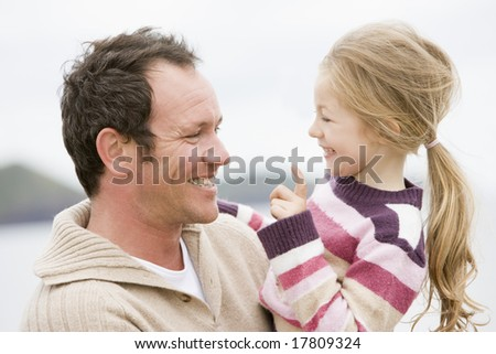 Father and daughter at beach smiling - stock photo