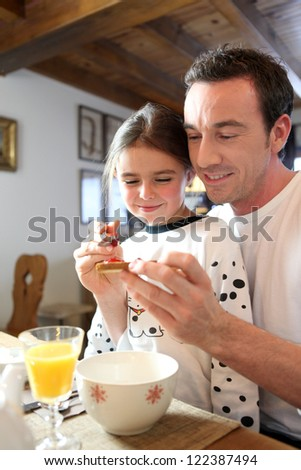 Father and daughter at breakfast - stock photo