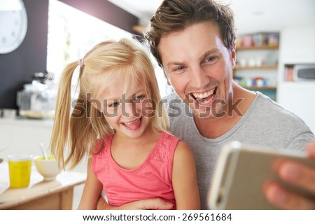 Father And Daughter At Posing For Selfie At Breakfast Table - stock photo