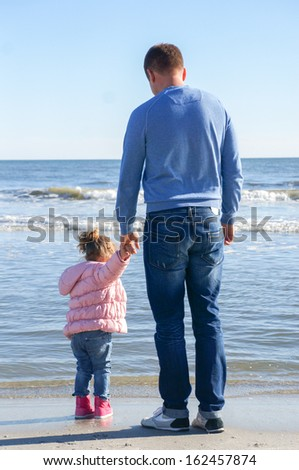 father and daughter at the ocean in autumn
