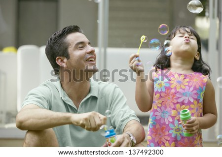 Father and daughter blowing bubbles - stock photo