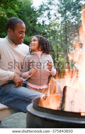 Father and daughter by fire - stock photo