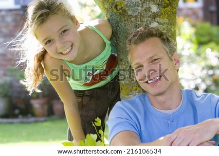 Father and daughter by tree, smiling, portrait