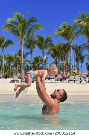 Father and daughter. Dad holding two year old baby girl in hands happy playing smiling in water on sea beach tropical vacation holidays - stock photo