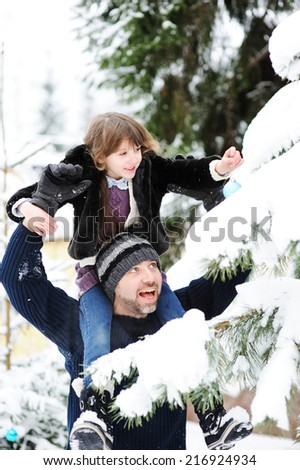 Father and daughter decorating Christmas tree  outdoor in the winter yard - stock photo