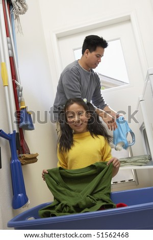 Father and daughter (7-9) doing laundry