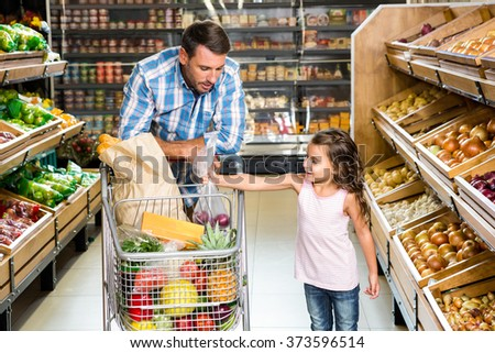 Father and daughter doing shopping in grocery store - stock photo