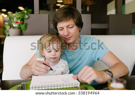 Father and daughter drawing a picture together indoors.