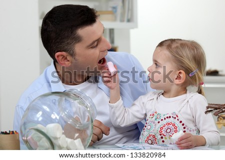 Father and daughter eating sweets - stock photo