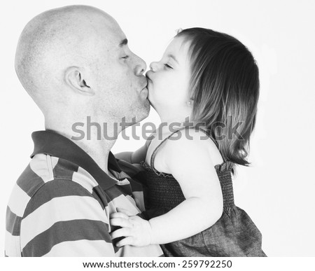 Father and daughter embrace and kiss on studio background - stock photo