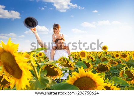 Father and daughter enjoying leisure time in a sunflower field. - stock photo
