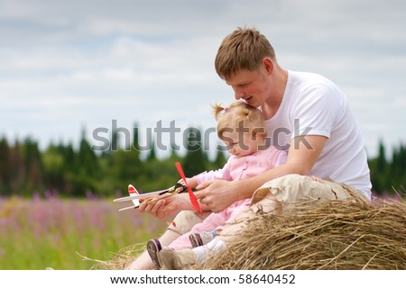 Father and daughter have fun with toy aircraft model on haystack - stock photo