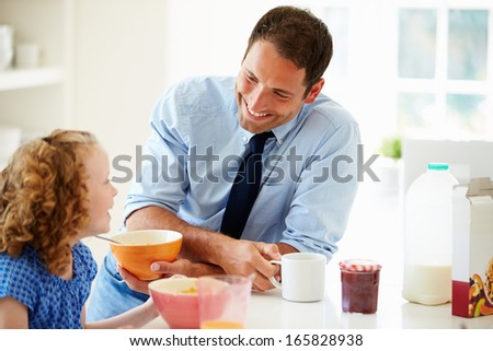 Father And Daughter Having Breakfast In Kitchen Together - stock photo