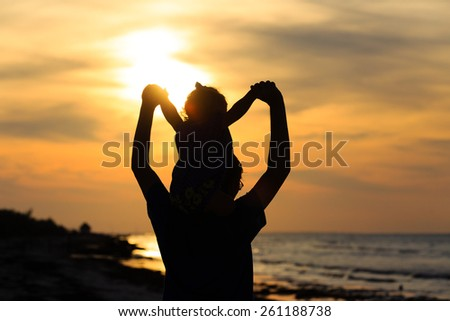 father and daughter having fun on sunset beach - stock photo