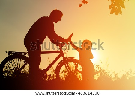 father and daughter having fun riding bike at sunset, active family sport