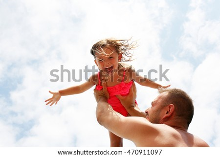 Father and daughter having fun together on the beach.