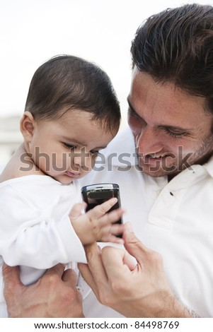 father and daughter holding and looking at the mobile phone. - stock photo