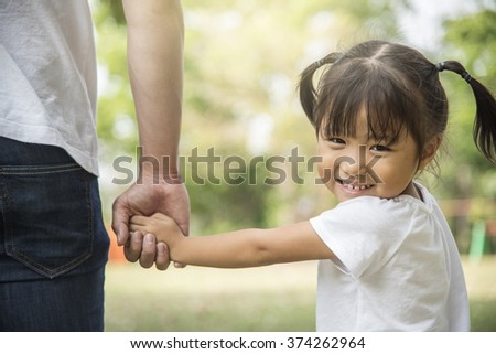 Father and daughter holding hand in hand - stock photo