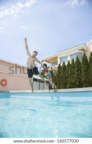 Father and daughter holding hands and jumping into pool - stock photo