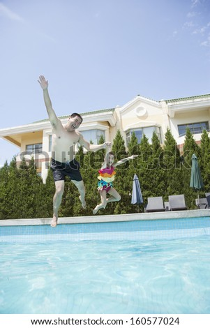 Father and daughter holding hands and jumping into the pool - stock photo