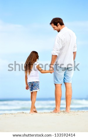 Father and daughter holding hands on the beach together happy and loving vacation - stock photo