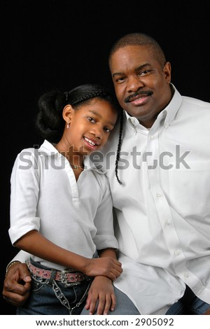 Father and daughter in a vertical portrait over a black background