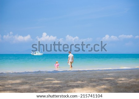 Father and daughter in swimming suit play on ocean beach with yacht on back