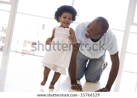 Father and daughter indoors playing and smiling - stock photo