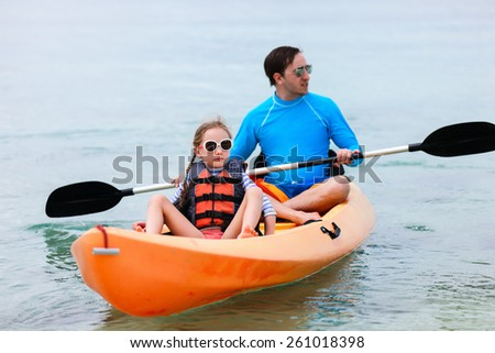Father and daughter kayaking at tropical ocean - stock photo