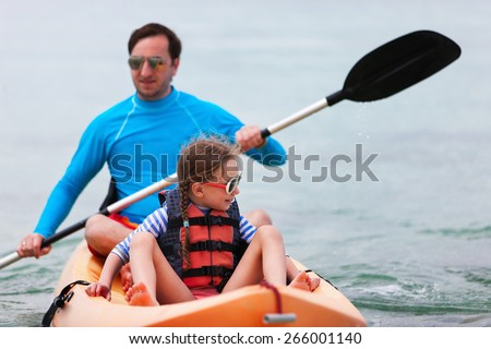 Father and daughter kayaking at tropical ocean on summer vacation - stock photo
