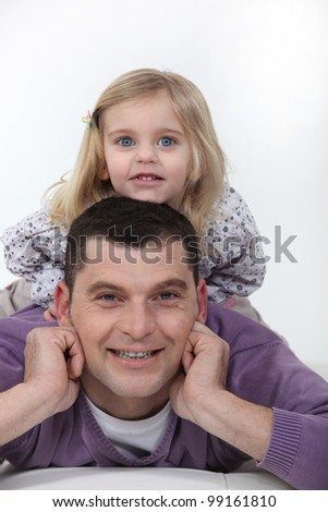 Father and daughter laying on bed - stock photo
